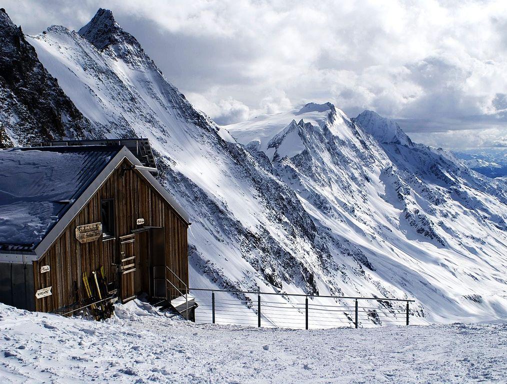 Zdjęcie: schron Holandia. Mały drewniany budynek ze spadzistym dachem na tle ośnieżonych szczytów.