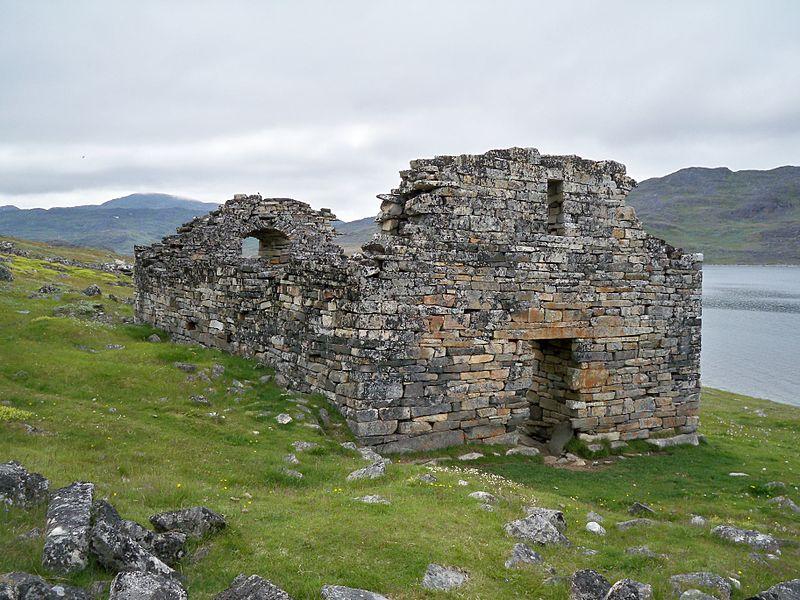 Zdjęcie: ruina kościoła Hvalsey, widać niewielką kamienną budowlę bez dachu, wokół trawa, w tle woda.