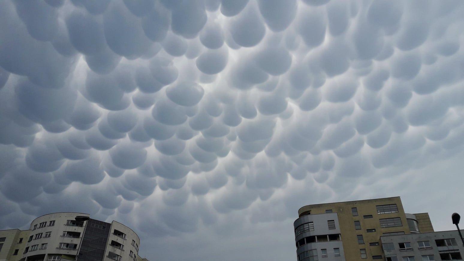 Zdjęcie: Na niebie chmury wyglądające jak dziesiątki wystających z nieba bąbli, w dole budynki.