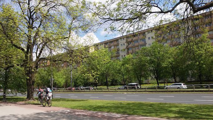 Zdjęcie: ulica Grójecka w Warszawie, rozdzielone pasy ruchu, po obu stronach pasy zieleni z drzewami.