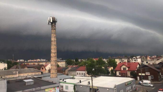 djęcie: wał szkwałowy w Mińsku Mazowieckim, krajobraz miejski z niskimi domami, na niebie ciemna, masywna, tworząca wał chmura.