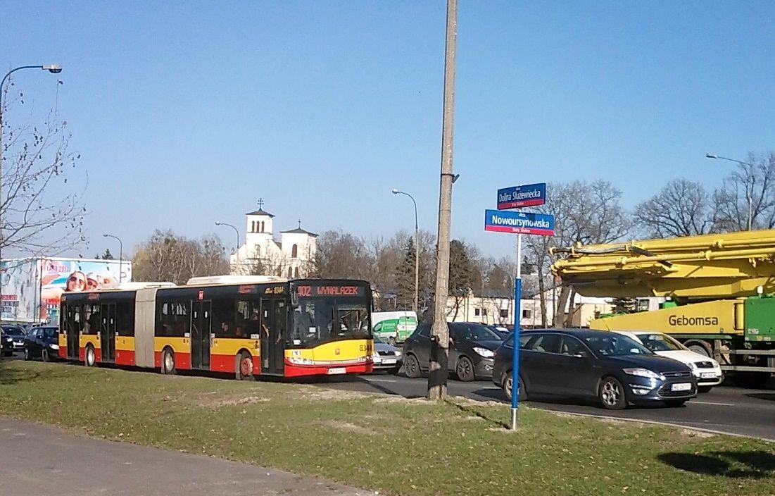 Zdjęcie: ulica w Warszawie, liczne samochody i autobus przegubowy.