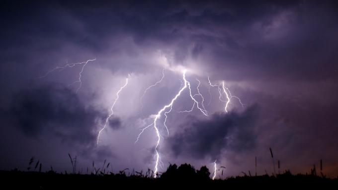 Zdjęcie: burza - nocne niebo rozświetlone rozległą błyskawicą.