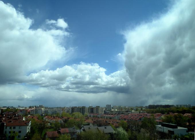 Zdjęcie: chmury konwekcyjne nad Warszawą, widać miejski krajobraz z kilkupiętrowymi domami, na niebie skłębione chmury, z niektórych pada deszcz