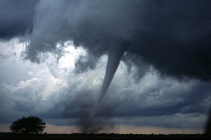 Zdjęcie: trąba powietrzna (tornado), widoczny wąski lej zwisający z chmury do powierzchni Ziemi.