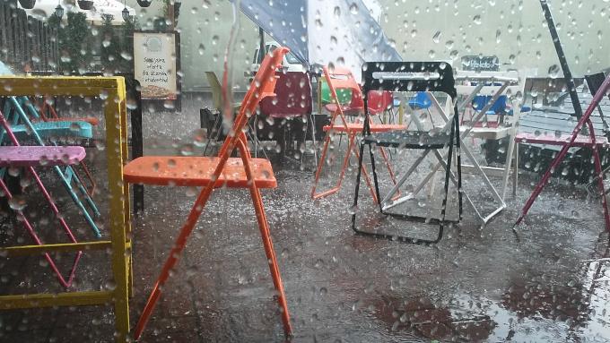 Zdjęcie: ulewa w Warszawie. Widać krzesełka i pochylony parasol w ogródku kawiarnianym, przesłonięte kroplami deszczu.