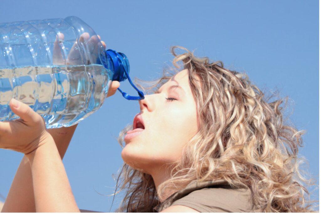 Zdjęcie: kobieta przygotowująca się do picia wody z pięciolitrowego baniaka.