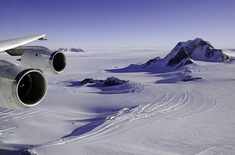 Zdjęcie: Antarktyda Zachodnia, Ziemia Marie Byrd. Widać skrzydło samolotu, z którego zrobiono zdjęcie i  pokryty śniegiem, pofałdowany krajobraz z pojedynczymi górami.
