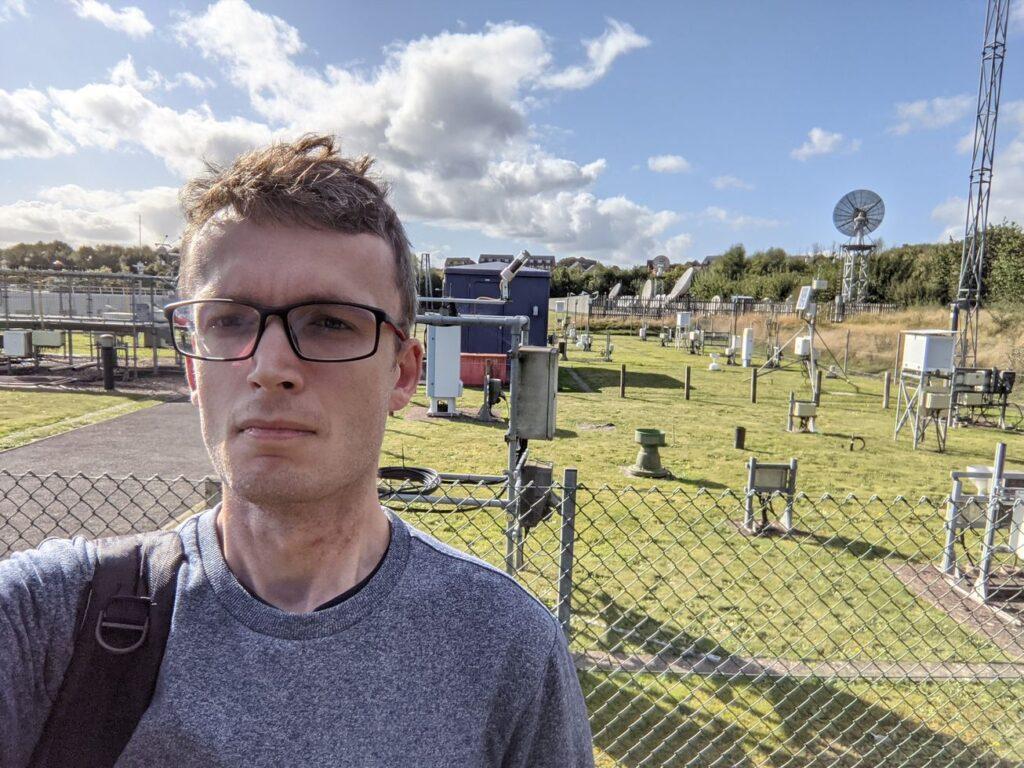 Zdjęcie: Piotr Florek na tle ogródka meteorologicznego, młody mężczyzna w okularach a w tle ogrodzony trawnik, na którym rozstawiono wiele przyrządów – skrzyneczek, anten itd.