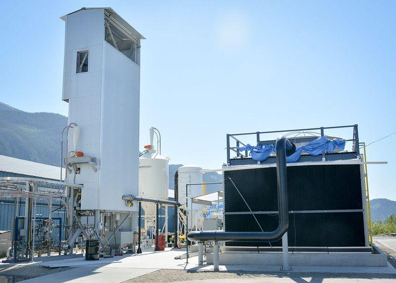 Zdjęcie: instalacja do wychwytu CO2 z powietrza firmy Carbon Engineering. Prostopadłościenna wieża wysokości ok. 3 pięter, dwa cylindryczne zbiorniki, prostopadłościenny kontener połączone rurami.]