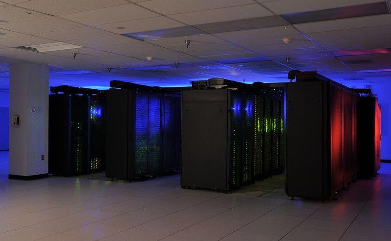 Zdjęcie: superkomputer NASA, widać ciemne pomieszczenie wypełnione czarnymi szafami, rozświetlanymi przez niebieskie, zielone i czerwone światełka.