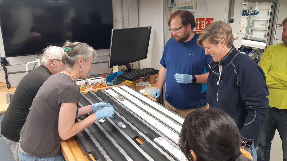 Zdjęcie: naukowcy oglądają próbki osadów dennych, dwie kobiety i dwóch mężczyzn pochyla się na dużym stołem z podłużnymi korytkami, częściowo wypełnionymi białym materiałem.