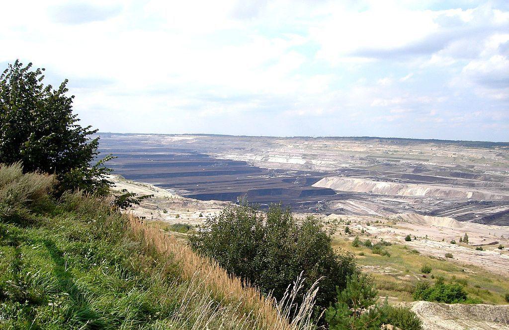 Zdjęcie: kopalnia odkrywkowa w Bełchatowie. Rozległy obszar wzgórków i zagłębień o geometrycznych kształtach.